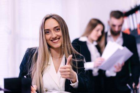 Photo pour Pouce levé femme souriante au bureau. collègues sur fond. - image libre de droit