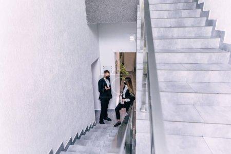 Photo pour Jeune homme d'affaires en masque de protection discutant du travail avec la femme d'affaires dans le couloir de bureau - image libre de droit