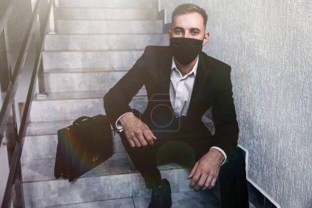 Photo pour Perdre son emploi. Travailleur injuste avec masque de protection assis sur l'escalier et regardant sérieusement la caméra. crise des entreprises, concept de travail et de soins de santé. - image libre de droit