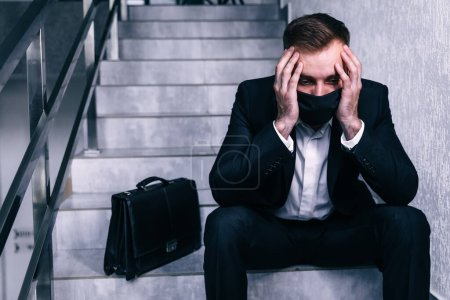 Photo pour Homme d'affaires porter un masque facial et chercher son prochain emploi - il est renvoyé en raison de la crise économique due à la propagation du coronavirus - image libre de droit