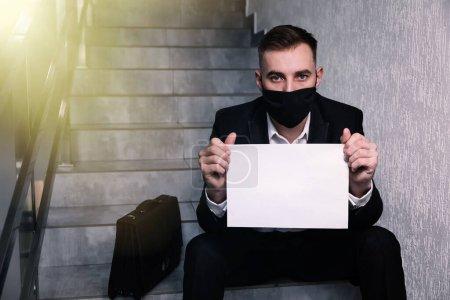 Photo pour L'homme porte un masque assis sur l'escalier à côté de sa mallette et tient une affiche vide. espace de copie - image libre de droit