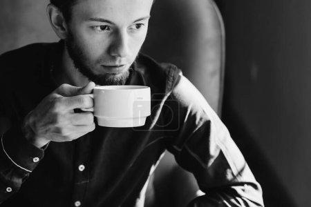 Photo pour Bel homme qui boit du café sur un fauteuil, photo noir et blanc. - image libre de droit