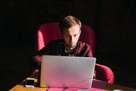 Photo pour Barbu gars en chemise de couleur marsala travaillant à l'ordinateur portable. lieu de travail, travail créatif. - image libre de droit