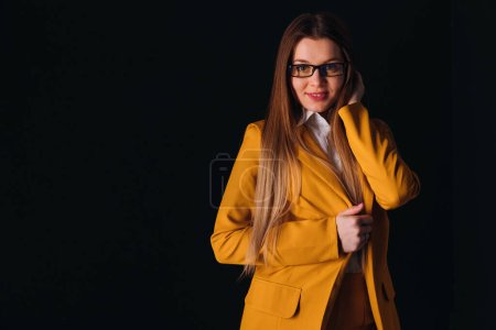 Photo for Beautiful woman with long hair wear yellow suit and eyeglasses. dark background. look at camera. - Royalty Free Image