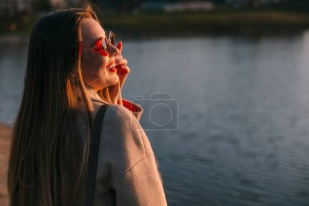 Photo for Young charming girl with a gorgeous shiny hair looks at beautiful lake on a sunset. Closeup portrait - Royalty Free Image