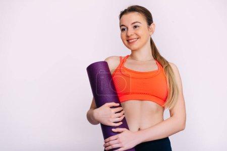 Photo pour Jeune femme de fitness attrayant prêt pour l'entraînement tenant tapis de yoga violet sur fond blanc. Place pour le texte. - image libre de droit