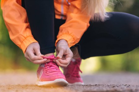 Photo for Young woman tying laces of running shoes before training - Royalty Free Image