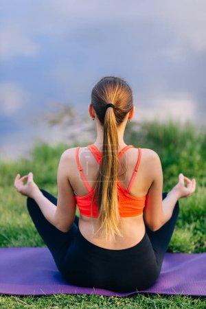 Photo pour Yoga fille détente méditation femme à l'extérieur sur l'été. Belle jeune modèle caucasien assis dans la pose de lotus dans l'herbe. - image libre de droit