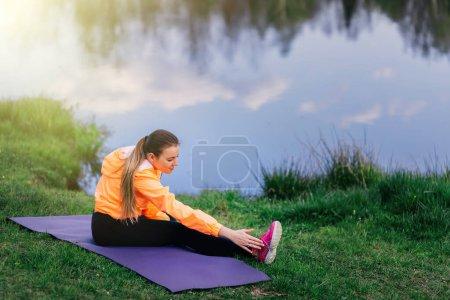 Photo pour Belle forme femme de yoga en leggings noirs pratique yoga stretch pose en plein air au bord du lac. Fitness, sport, personnes et mode de vie sain concept. - image libre de droit