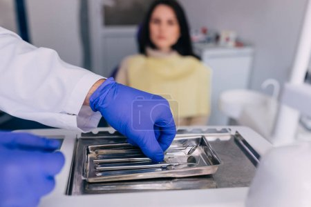 Photo for Dentist's hands with blue gloves work with a dental tools. the patient is sitting in a dental chair in the background. - Royalty Free Image