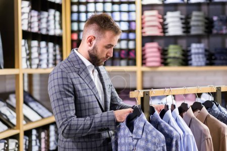 Photo for Young man in a stylish plaid suit, standing near the hangers in a boutique, choosing shirts. - Royalty Free Image