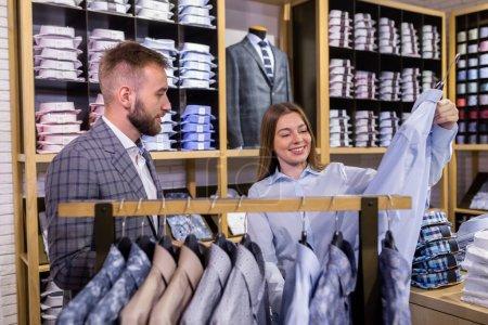 Photo pour Assistant consultante fille offre une variété de chemises dans un magasin de vêtements pour hommes - image libre de droit