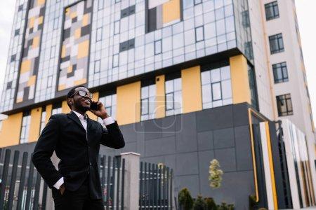 Photo pour Souriant jeune afro-américain adulte passe un appel d'affaires, parlant au téléphone dans la rue. - image libre de droit