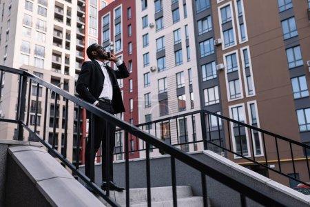 Photo pour Attrayant homme d'affaires habillé à la mode gauche immeuble de bureaux pour parler sur téléphone portable moderne sur la rue. - image libre de droit