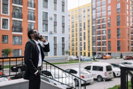 Photo pour A serious mature man, a businessman of a large company, dressed stylishly, talking on a cell phone, looking up and thinking about the next steps, solving work tasks. - image libre de droit