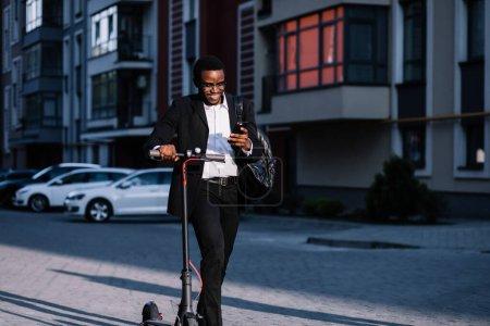 Photo pour Jeune étudiant avec un sac à dos derniers couples de retour à la maison en scooter électrique sur le trottoir. Transport alternatif - image libre de droit
