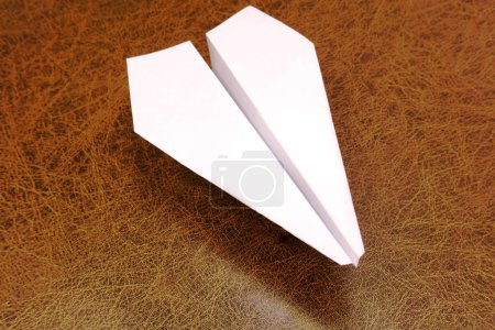 Photo for White paper airplane pierced with a dagger on a rough wooden shield - Royalty Free Image