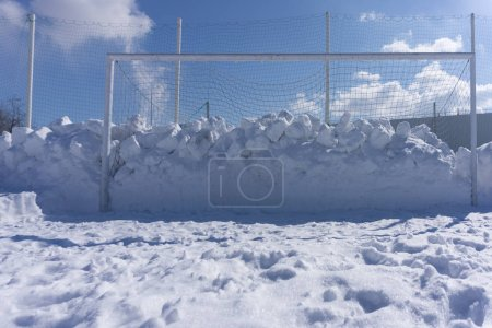 Football pitch soccer field in winter snow