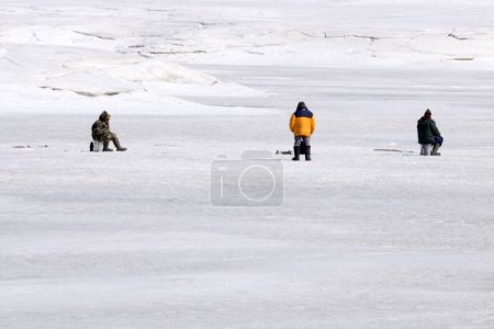 Fisherman makes a hole during the annual ice fishing competition, fishing for fishing tackle jig