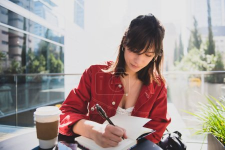Young happy woman at a coffee shop outdoors writing on a book