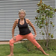 Smiling senior blond woman doing her stretches loo...