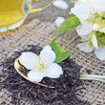 Jasmine flowers and fresh tea on wooden background...