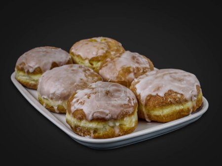 Traditional Polish donuts with icing over black background