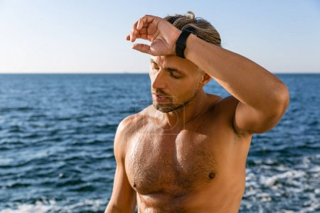 tired shirtless adult man wiping sweat from forehead after training on seashore