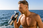 close-up portrait of shirtless wet man with fitness bottle of water on seashore