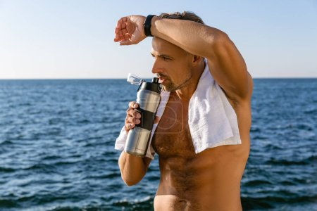 shirtless adult man with towel on shoulders drinking water and wiping sweat after workout on seashore