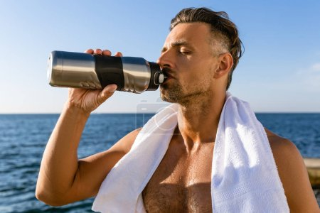 shirtless handsome adult sportsman with towel on shoulders drinking water after workout on seashore