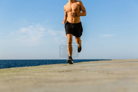 cropped shot of shirtless sportsman jogging on seashore