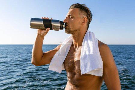 shirtless handsome adult sportsman with towel on shoulders drinking water after training on seashore