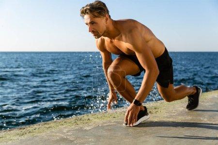 handsome adult shirtless sprint runner standing in start position for run on seashore
