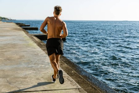 rear view of muscular shirtless sportsman jogging on seashore