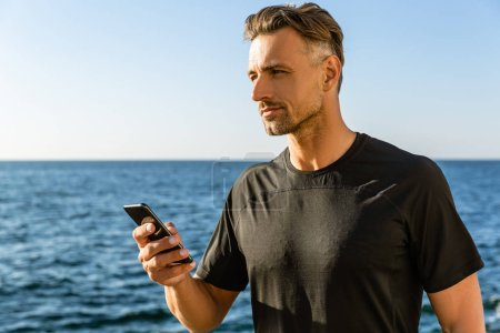 handsome adult man with smartphone on seashore and looking away