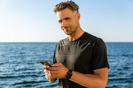 handsome adult man with smartphone on seashore and looking at camera