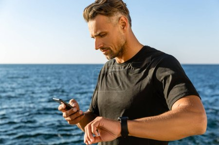 handsome adult man using smartphone and smart watch on seashore