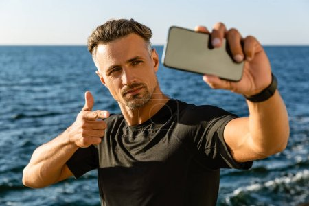 handsome adult man taking selfie with smartphone and pointing at camera on seashore