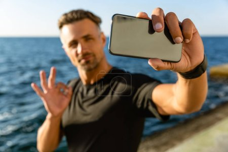 Photo for Handsome adult man taking selfie with smartphone and showing okay gesture on seashore - Royalty Free Image