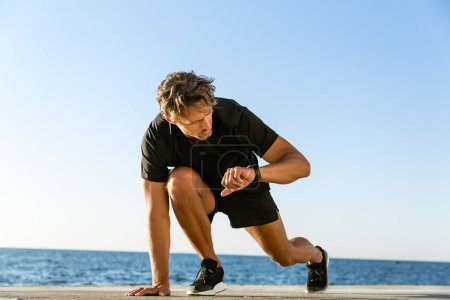 handsome adult sprint runner looking at fitness tracker while standing in start position for run on seashore