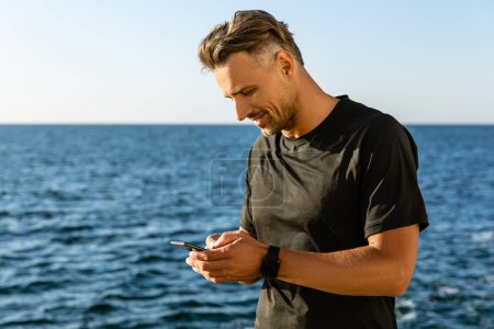 smiling adult man using smartphone on seashore