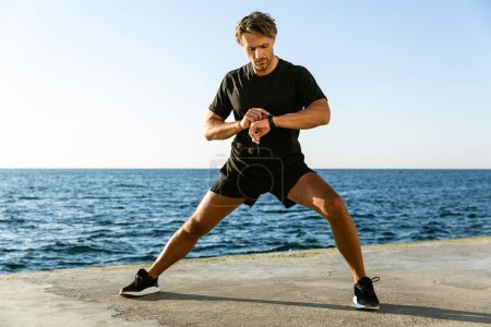 handsome adult sportsman looking at fitness tracker while stretching before training on seashore