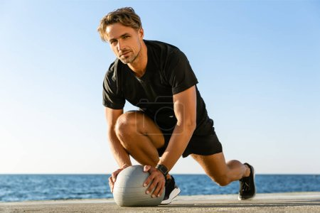handsome adult sportsman working out with fit ball on seashore
