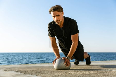 handsome adult sportsman doing push ups with fit ball on seashore and looking at camera