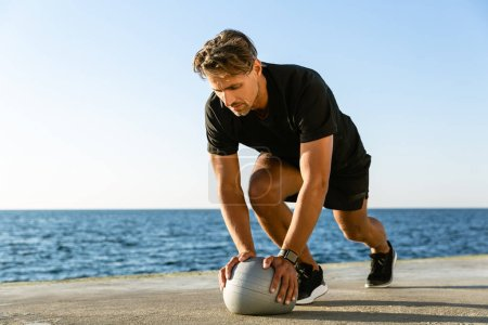 Photo for Handsome adult sportsman doing push ups with fit ball on seashore - Royalty Free Image