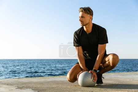 handsome adult sportsman sitting with fit ball on seashore and looking away