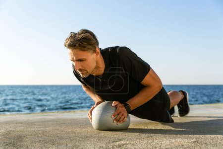 handsome adult sportsman doing push ups with fit ball on seashore