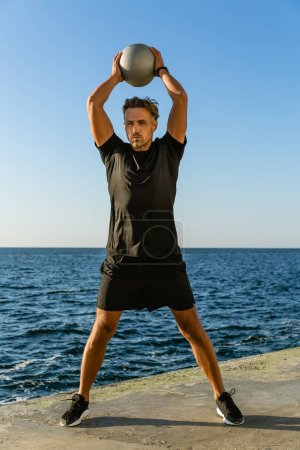 handsome adult sportsman working out with fit ball and holding it above head on seashore