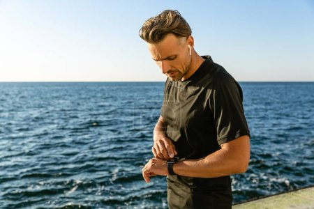 handsome adult man with wireless earphones checking results of training with smart watch on seashore